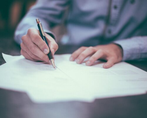 man's hands holding pen on paper