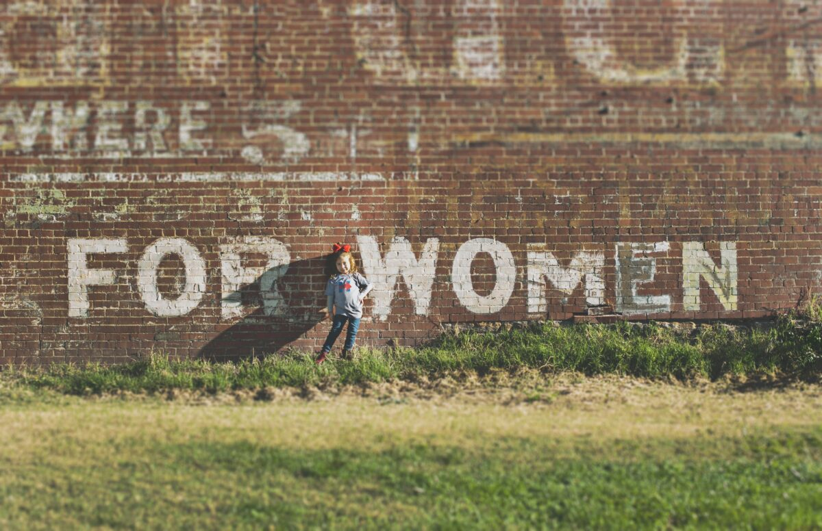 young girl standing in front of wall saying for women