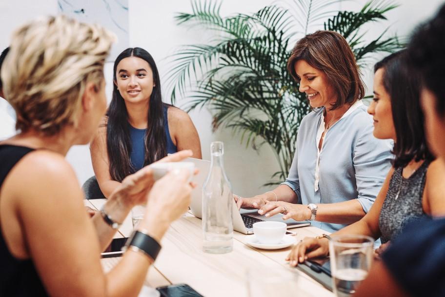 team members meeting around desk with laptop