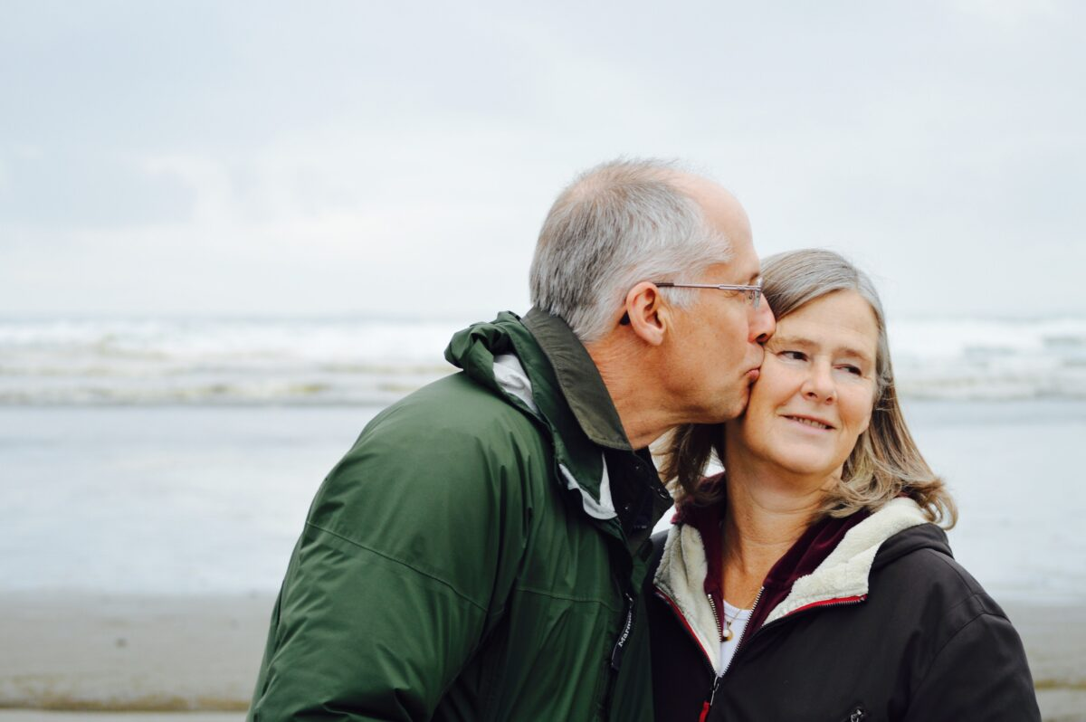 Older couple kissing on a beach
