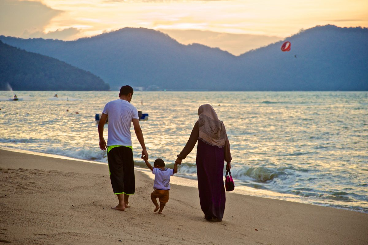 man, child and woman holding hands walking on a beach