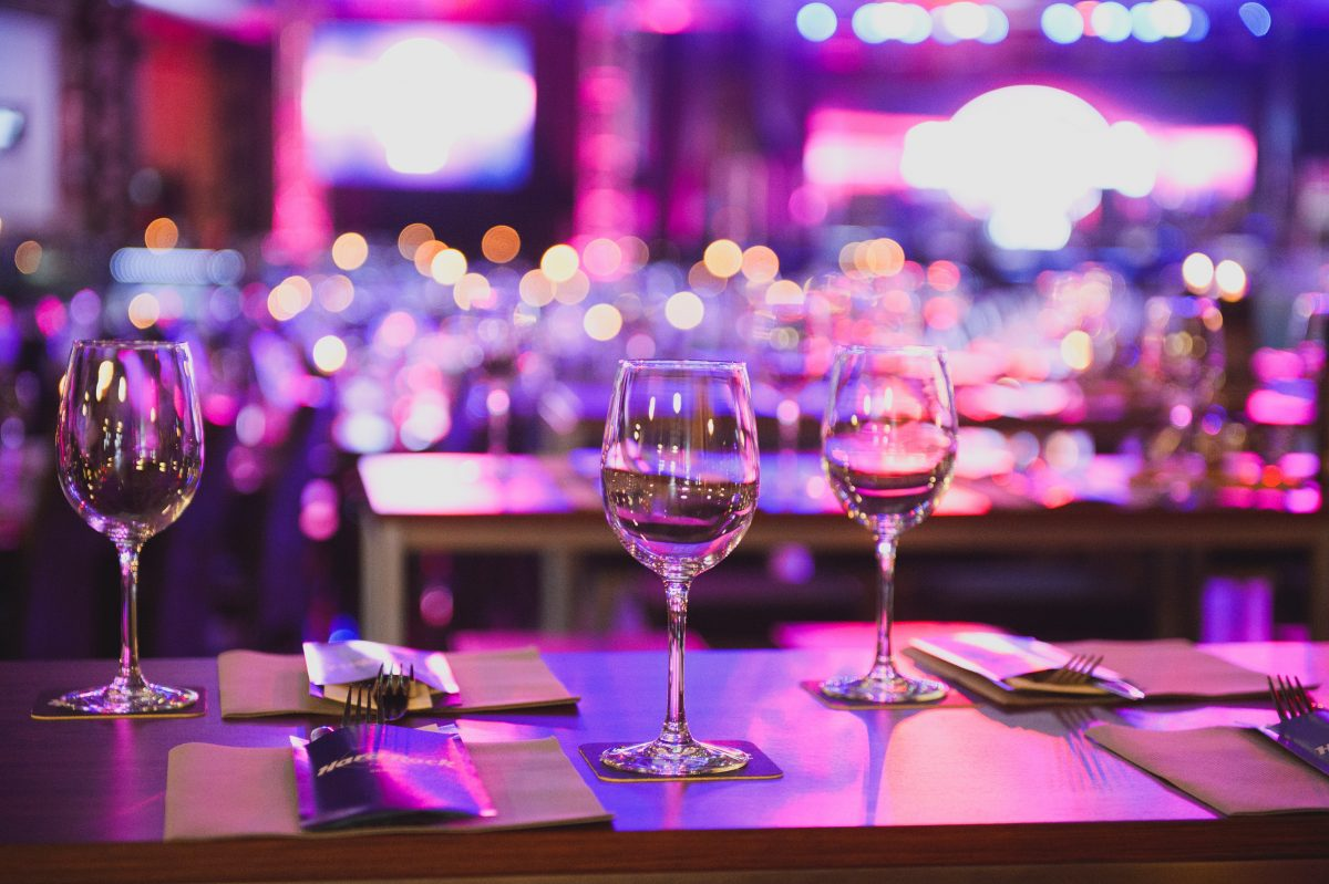 wine glasses on table with lights behind
